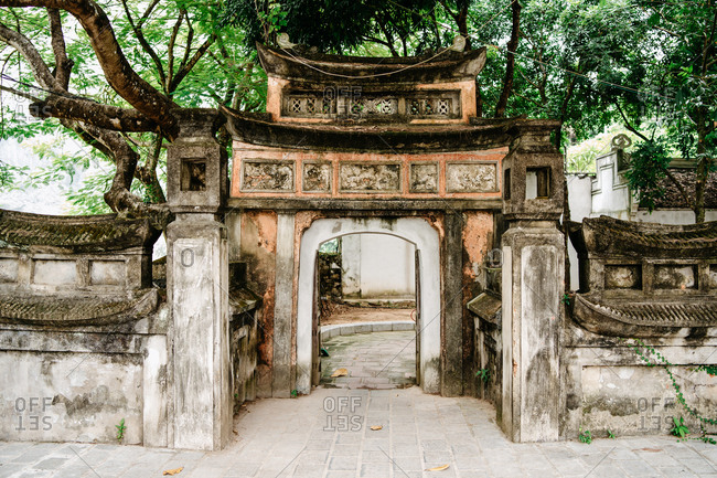 Exterior of stone arch entrance of old temple surrounded by tall trees in courtyard