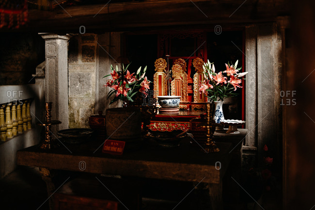Traditional ornate table with candlesticks and fresh water in bowl for worship placed in temple in Vietnam