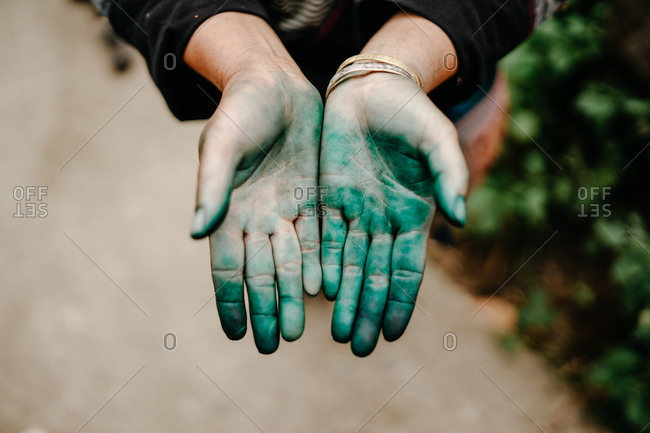 Top view of female standing on city street and demonstrating hands in green powder after Hindu festival