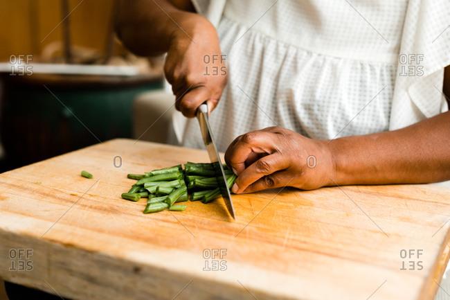 Woman chopping green beans on a cutting board