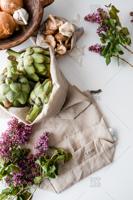 Fresh produce on white surface with linen sack and lilacs