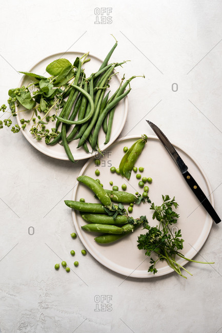 Green beans, peas and herbs on white plate with knife