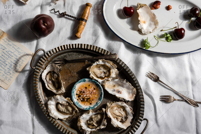 Oyster dish on table with white cloth and cherries