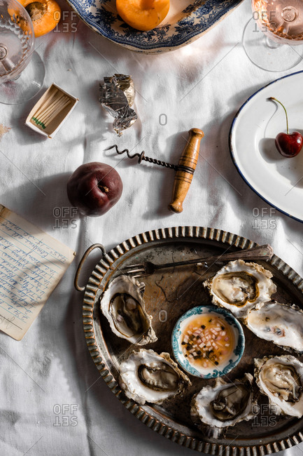 Oysters in a rustic dish on table with white cloth and fruit