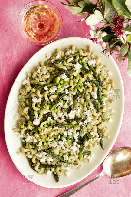 Roasted asparagus pea pasta with fresh pea pesto sauce served with wine