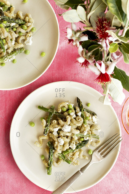 Roasted asparagus pea pasta with fresh pea pesto sauce served on plates by flowers