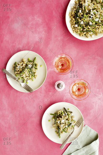 Roasted asparagus pea pasta with fresh pea pesto sauce served with wine on pink background