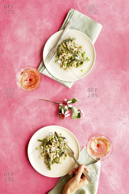 Person eating roasted asparagus pea pasta with fresh pea pesto sauce on pink background