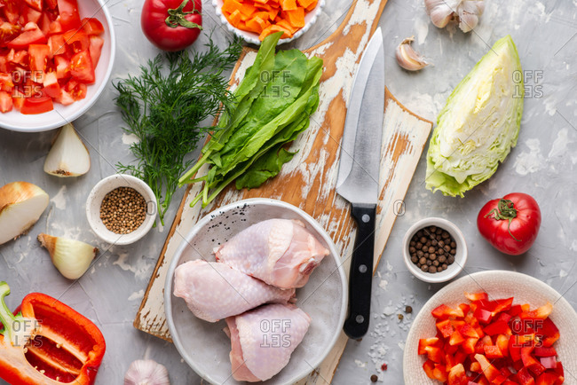 Raw chicken legs with fresh vegetables and spices on gray background. Ingredients for cooking chicken dish