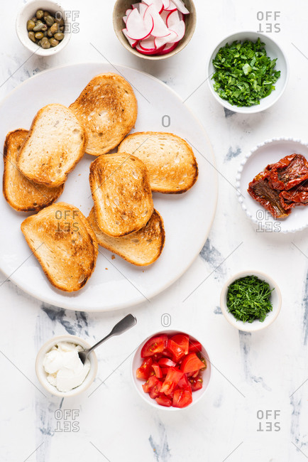 Plate full of fresh toasts with vegetables and cream cheese over white background. Ingredients for sandwiches