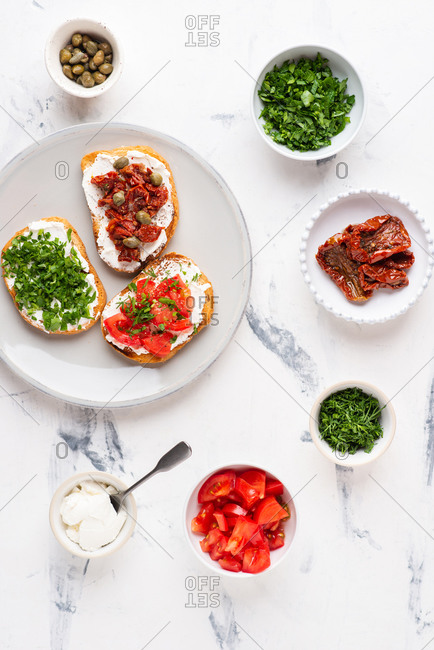 Variety of sandwiches with vegetables and cream cheese over white background