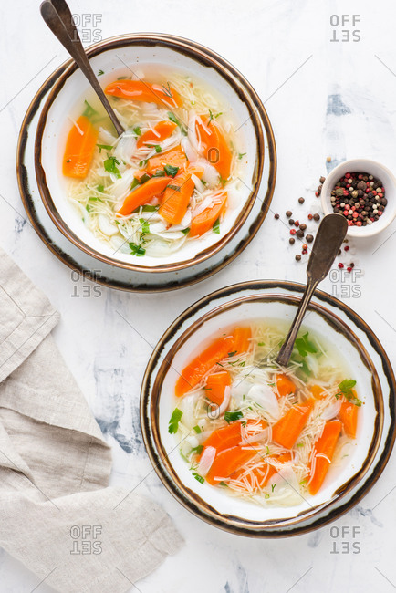 Noodle vegetarian soup with carrot, onion and dill over white background