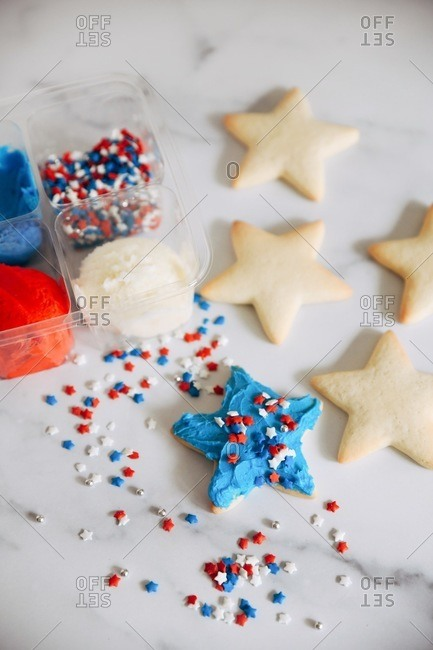 Star shaped sugar cookies with red, white and blue sprinkles and frosting