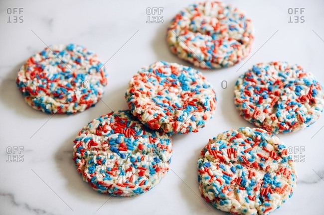 Red, white and blue sprinkle cookies on marble surface