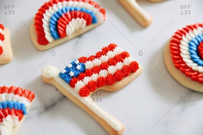 Close up of American flag and bunting sugar cookies on marble surface