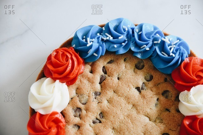 Close up of a festive 4th of July chocolate chip cookie cake with red, white and blue frosting