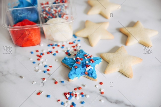 Close up of a DIY star shaped sugar cookie kit with red, white and blue sprinkles and frosting