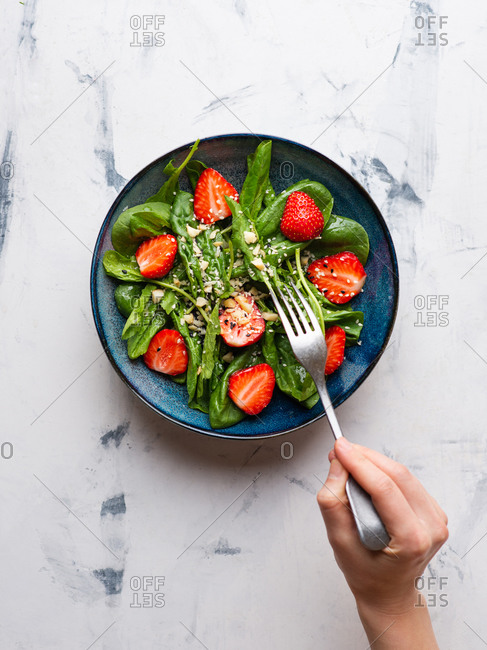 Strawberry salad with spinach, nuts, sesame seeds and green leaf cress salad. Hand with fork grabbing salad