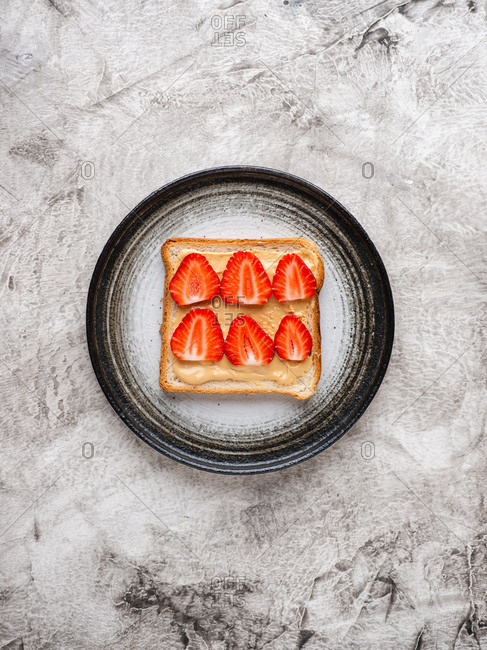 Peanut butter and strawberry sandwich served on plate