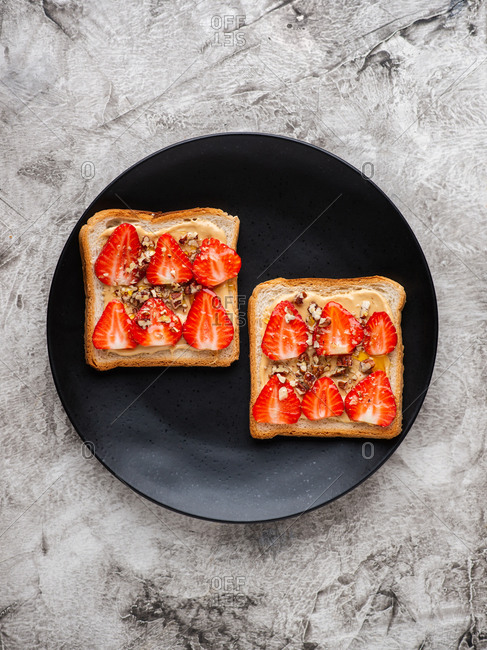 Peanut butter and strawberry sandwiches with ground pecan nuts and honey