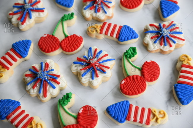 Firework and cherry sugar cookies on marble surface