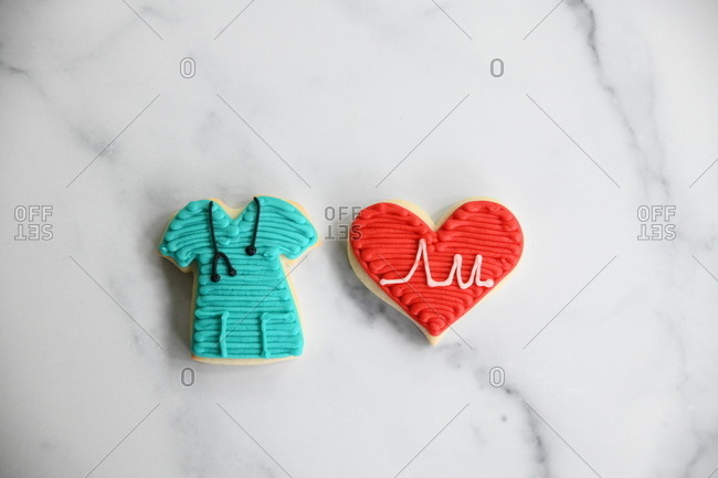 Sugar cookies in the shape of a heart and hospital scrubs