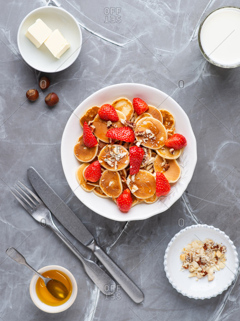 Mini pancakes served in white bowl with fresh strawberry, bananas, nuts, butter and honey