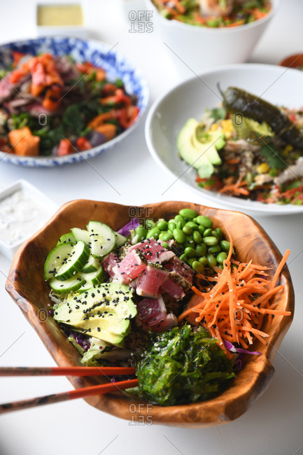 Gourmet dishes on white surface with focus on a tune poke bowl