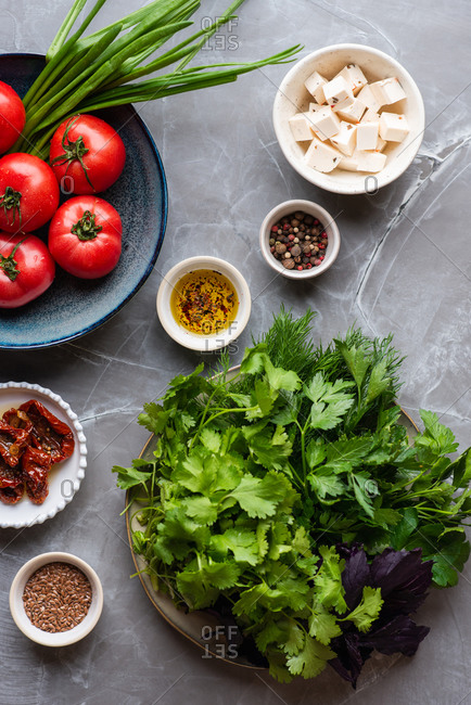 Vegetable salad ingredients. Tomatoes, fresh herbs, spices and cheese