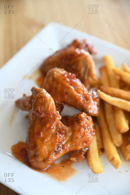 Chicken wings dripping with sauce served with French fries