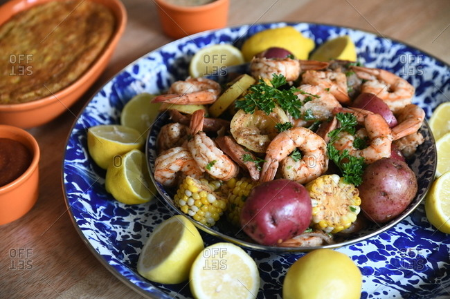 Shrimp boil with potatoes and corn in a blue dish