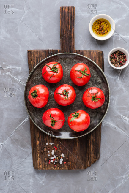 Plate with fresh ripe tomatoes placed on wooden cutting board over gray background
