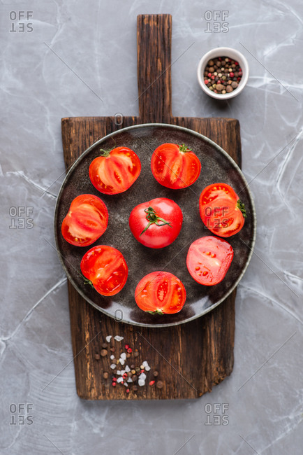 Halved and whole fresh tomatoes placed on wooden cutting board on gray background