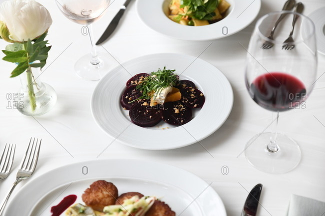 Gourmet beet and scallop dishes served in a restaurant with wine