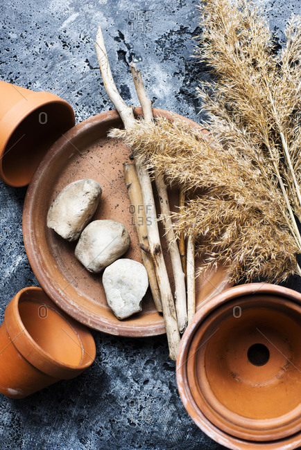 Terra-cotta pots, sticks, harvest grass stalks and stones