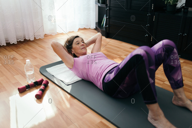 Elderly woman doing sit ups at home. Wide angle shot of 70 years old woman with hands behind her head lying on fitness mat exercising push ups in her living room.