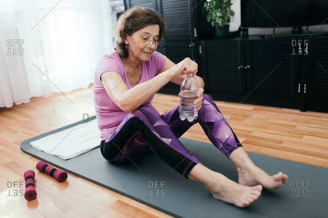 Senior woman is going to drink water after workout at home. Tired elderly woman in purple sportswear sitting on fitness mat opening bottle with water after workout in living room.