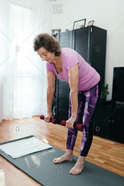 Active elderly woman doing workout at home. Full length shot of focused 70 years old woman in purple sportswear training her back holding dumbbells both hands in living room.