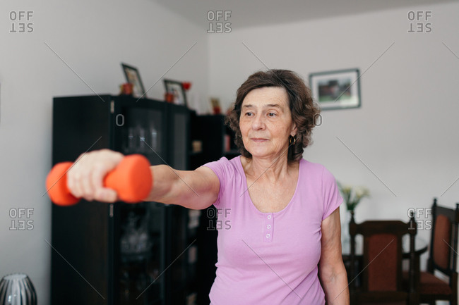 Active senior woman exercising at home. Waist up shot of 70 years old focused retired woman lifting dumbbell with her right arm in living room.
