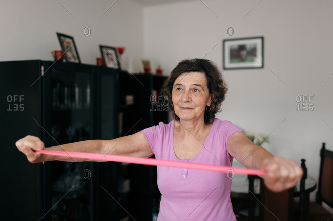 Elderly woman stretching rubber band at home. Waist up shot of 70 years old woman in purple t-shirt exercising arms with pink rubber band in living room.