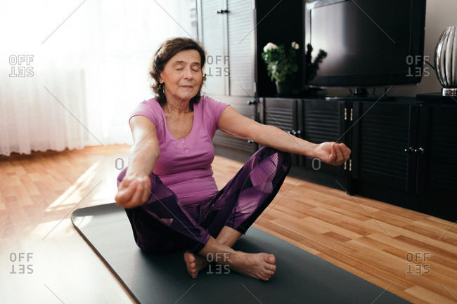 Focused senior woman doing yoga at home. 70 years old woman sitting on fitness mat with outstretched hands resting on her knees performing yoga in living room.