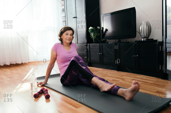 Senior woman performing exercise in living room. Elderly woman in pink sportswear sitting on fitness mat doing stress and pain relief exercising at home.