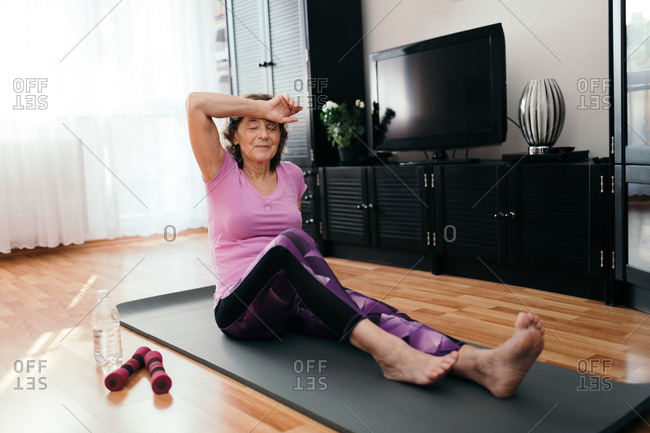 Tired elderly woman after exercise at home. Weary senior woman in purple sportswear sitting on fitness mat wipes sweat from her forehead after workout in living room.
