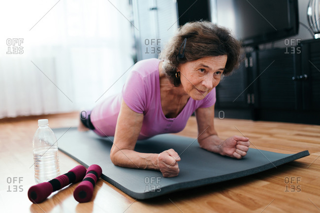 Senior woman workout at home. Low angle shot of elderly woman at her 70s lying on fitness mat exercising plank indoors.