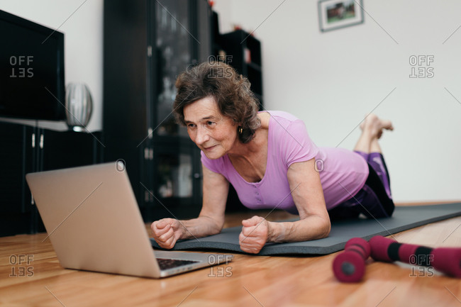 Elderly woman exercising at home watching online course. Low angle shot of senior woman at her 70s lying on floor exercising plank while watching fitness training online on notebook at home.