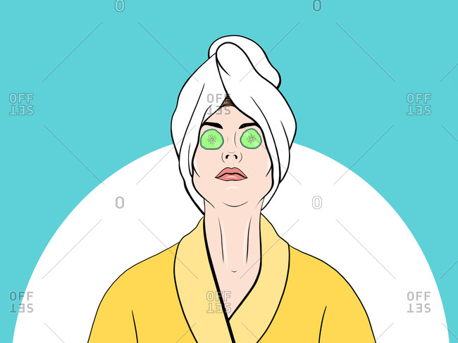 Young woman in yellow bathrobe with a facial mask and cucumber slices on her eyes after shower