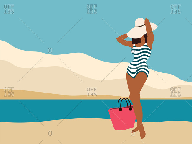Elegant girl in continuous striped swimsuit and in wide-brimmed hat is standing on the beach near the water