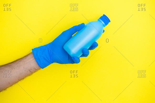 Unrecognizable doctor with surgical gloves holding sanitizing on yellow background
