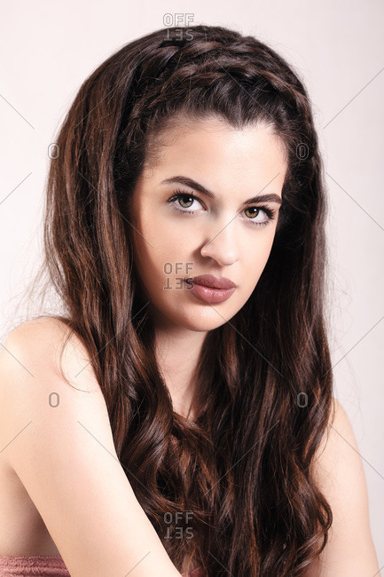 Portrait of beautiful young woman with long hair posing in a studio looking at camera