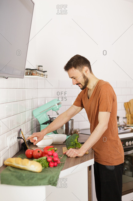 Man preparing recipe in kitchen while looking at tablet